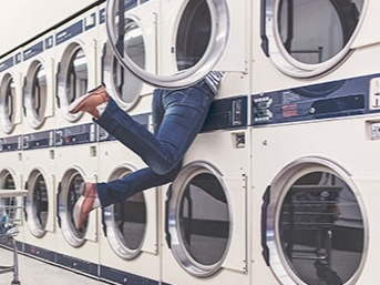 Image of a woman half inside a large washing machine